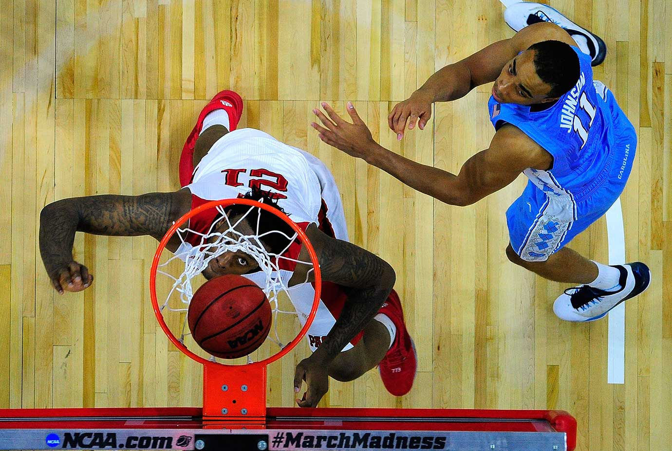 BeeJay Anya of North Carolina State watches his shot fall through the net against Brice Johnson of North Carolina.