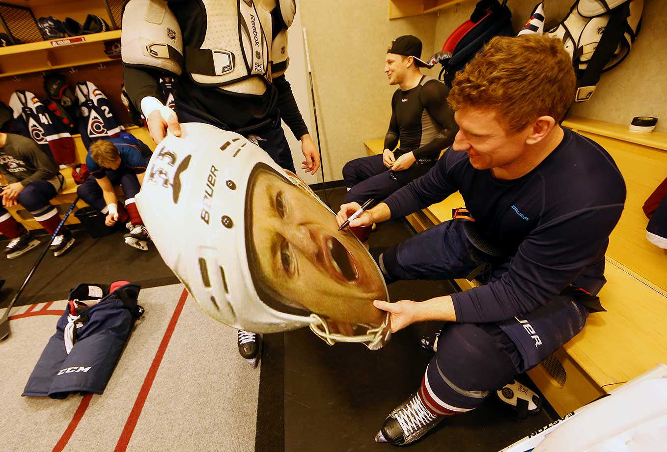 Cody McLeod of Colorado signs a cardboard cutout of his head for a fan prior to a game against San Jose.