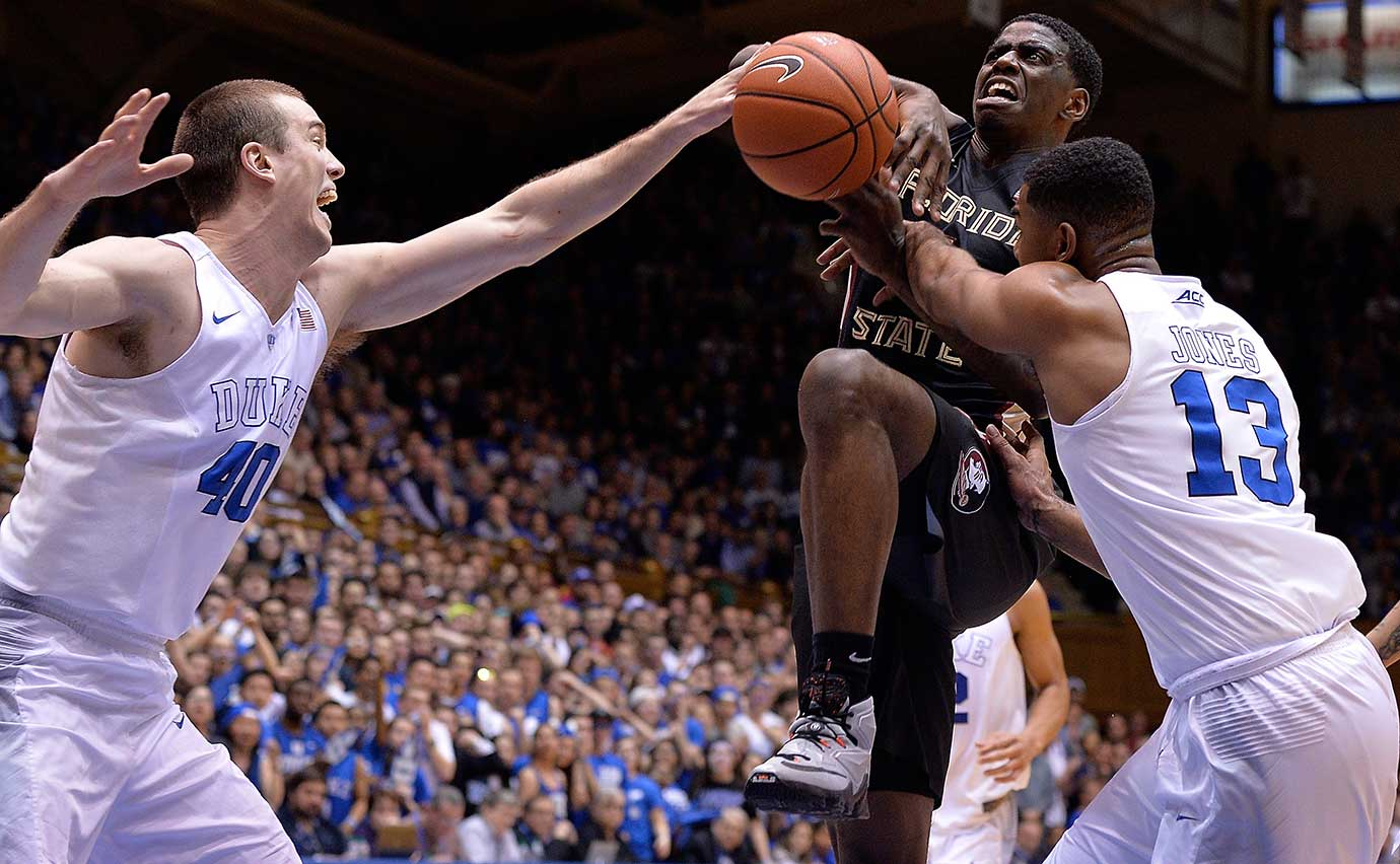Dwayne Bacon of Florida State is fouled as he drives between Marshall Plumlee, left, and Matt Jones of Duke.
