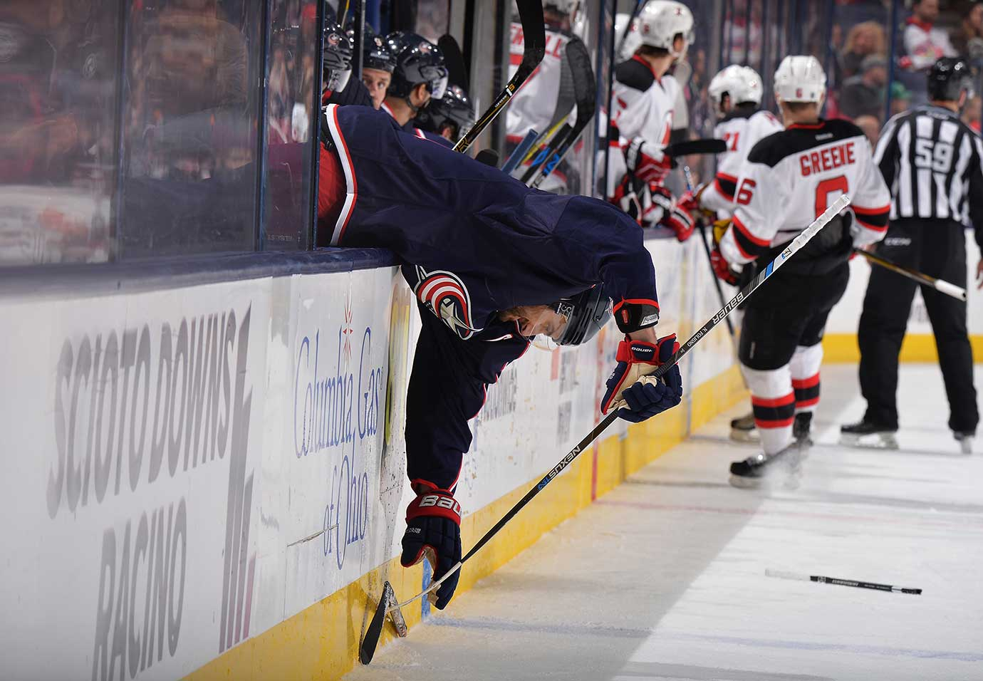 Nick Foligno of the Columbus Blue Jackets reaches over the boards to pick up a broken stick.