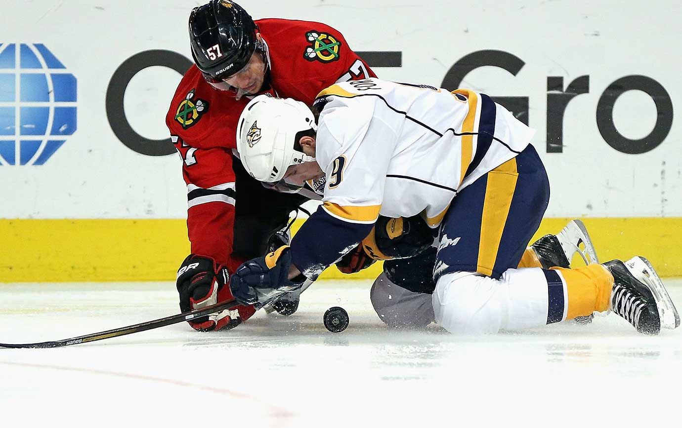 Filip Forsberg (9) of Nashville and Trevor van Riemsdyk of Chicago battle for the puck.