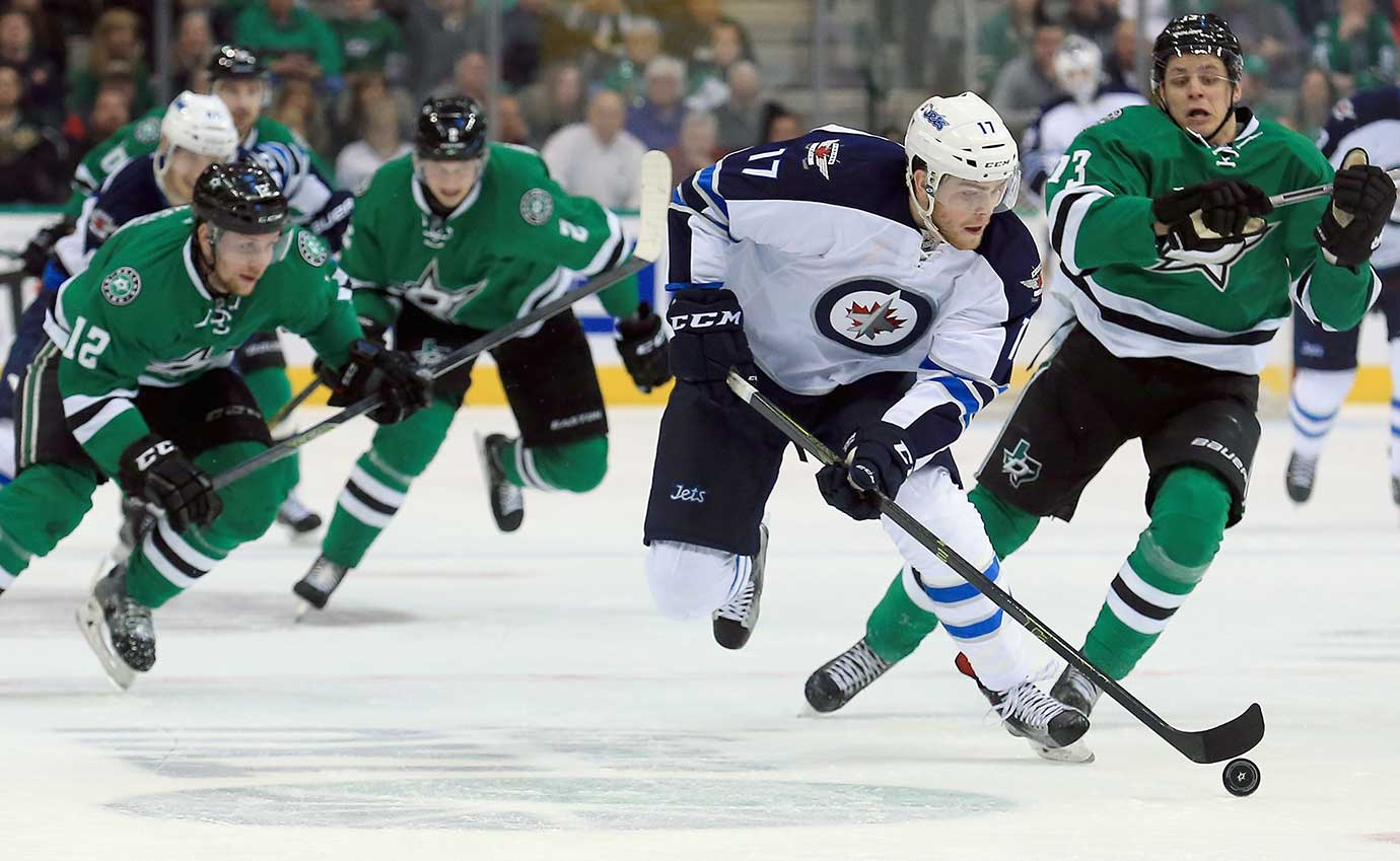 Adam Lowry of Winnipeg controls the puck against Mattias Janmark (13) of the Dallas Stars.