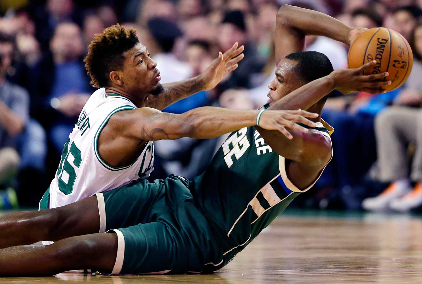 Milwaukee's Khris Middleton tries to pass while pressured by Marcus Smart of Boston.