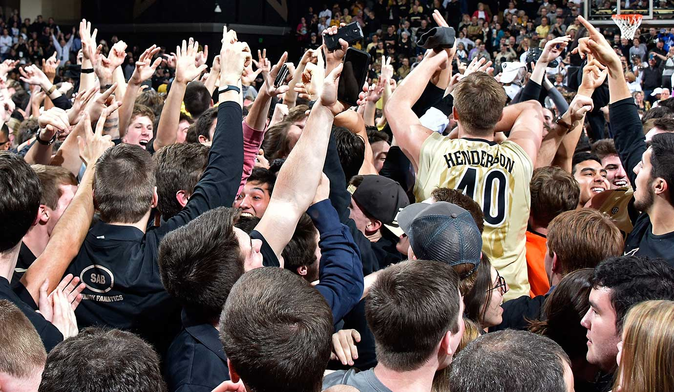 Josh Henderson of Vanderbilt high fives fans as they storm the court after Vandy's 74-62 upset of Kentucky.