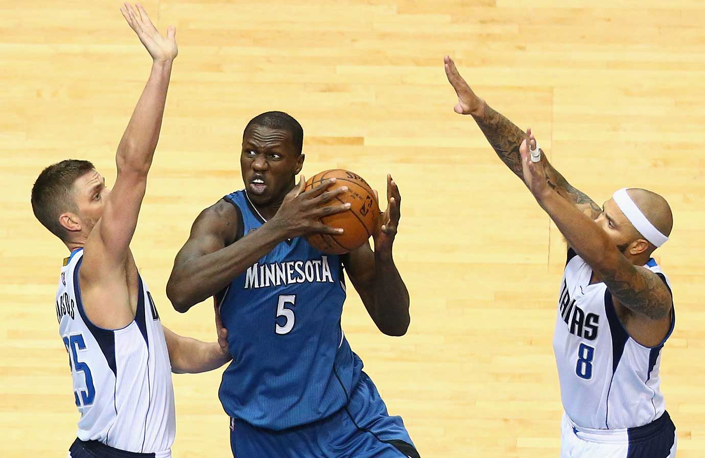 Gorgui Dieng of Minnesota dribbles against Chandler Parsons and Deron Williams of the Dallas Mavericks.