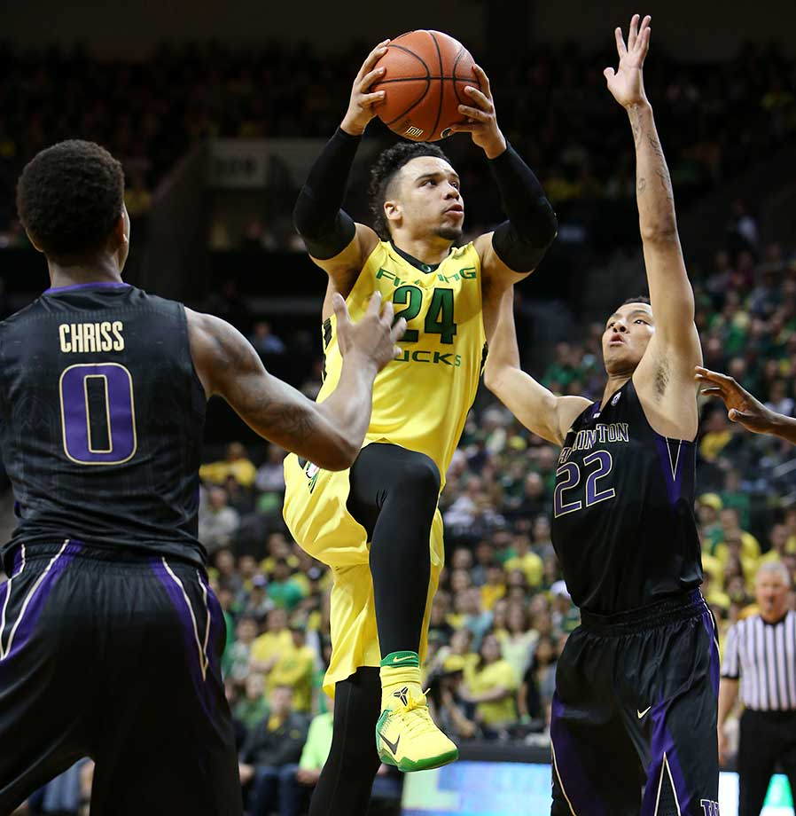 Oregon's Dillon Brooks drives to the basket between Washington's Marquese Chriss, left, and Dominic Green.