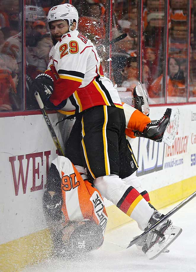 Chris VandeVelde of the Philadelphia Flyers is checked by Deryk Engelland of Calgary.