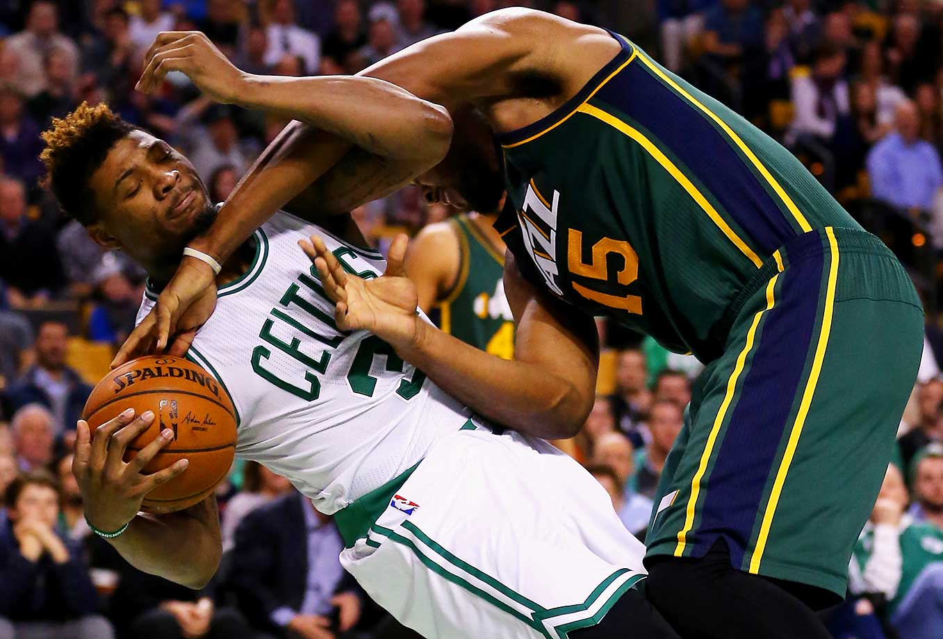Marcus Smart of the Boston Celtics and Derrick Favorsof the Utah Jazz battle for a loose ball.