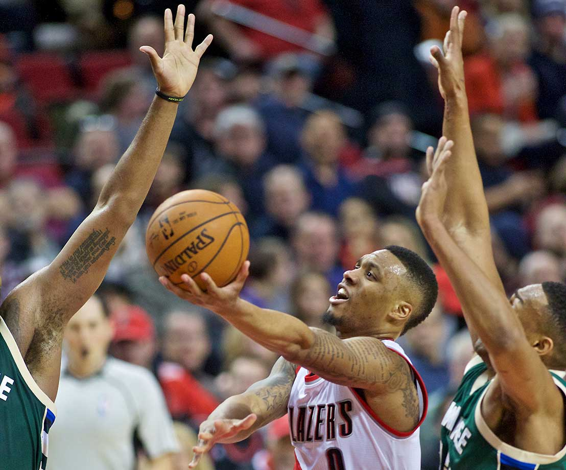 Portland Trail Blazers guard Damian Lillard shoots in front of Milwaukee Bucks forward Jabari Parker, right, in Portland, Ore.