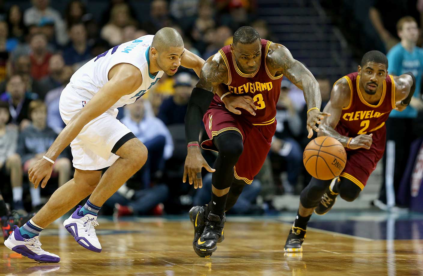 Kyrie Irving watches as LeBron James and Nicolas Batum hustle for a loose ball.
