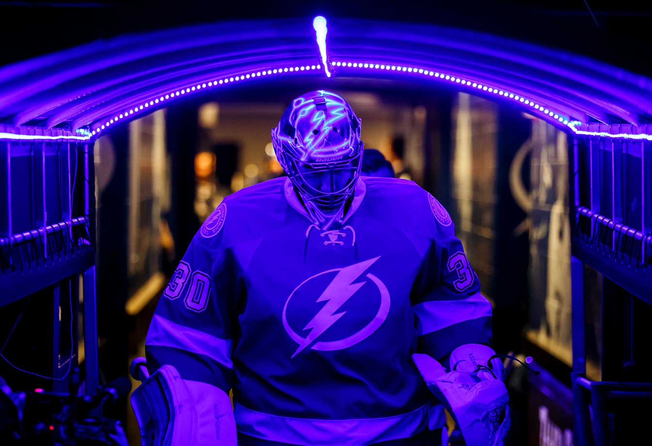 Goalie Ben Bishop of the Tampa Bay Lightning walks through a blue lit tunnel before pregame warmups against the Detroit Red Wings at the Amalie Arena.