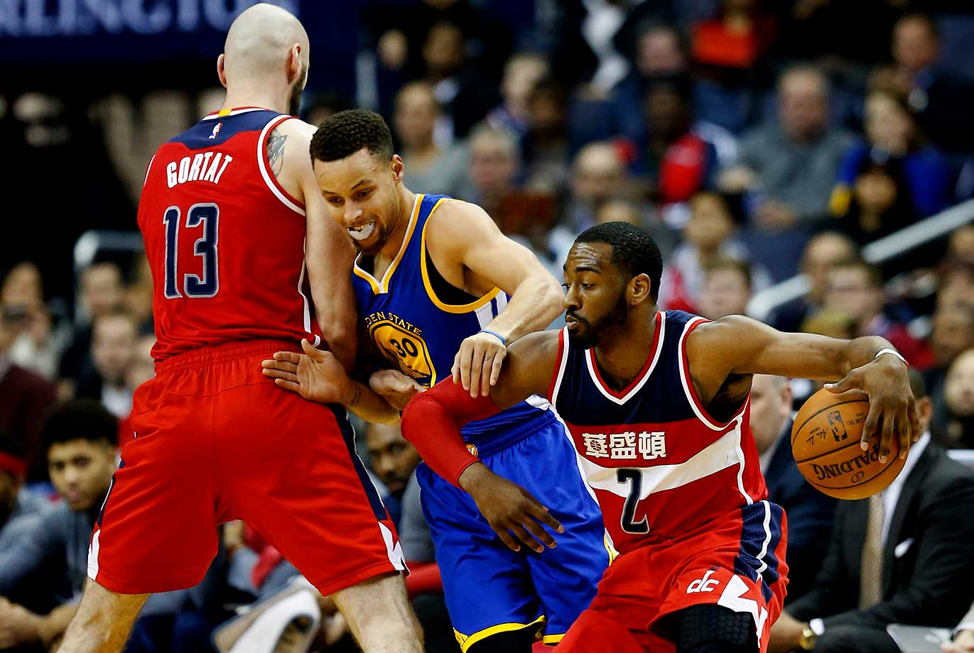 John Wall of the Washington Wizards drives around Stephen Curry of the Golden State Warriors and Marcin Gortat of the Washington Wizards at Verizon Center in Washington, D.C.