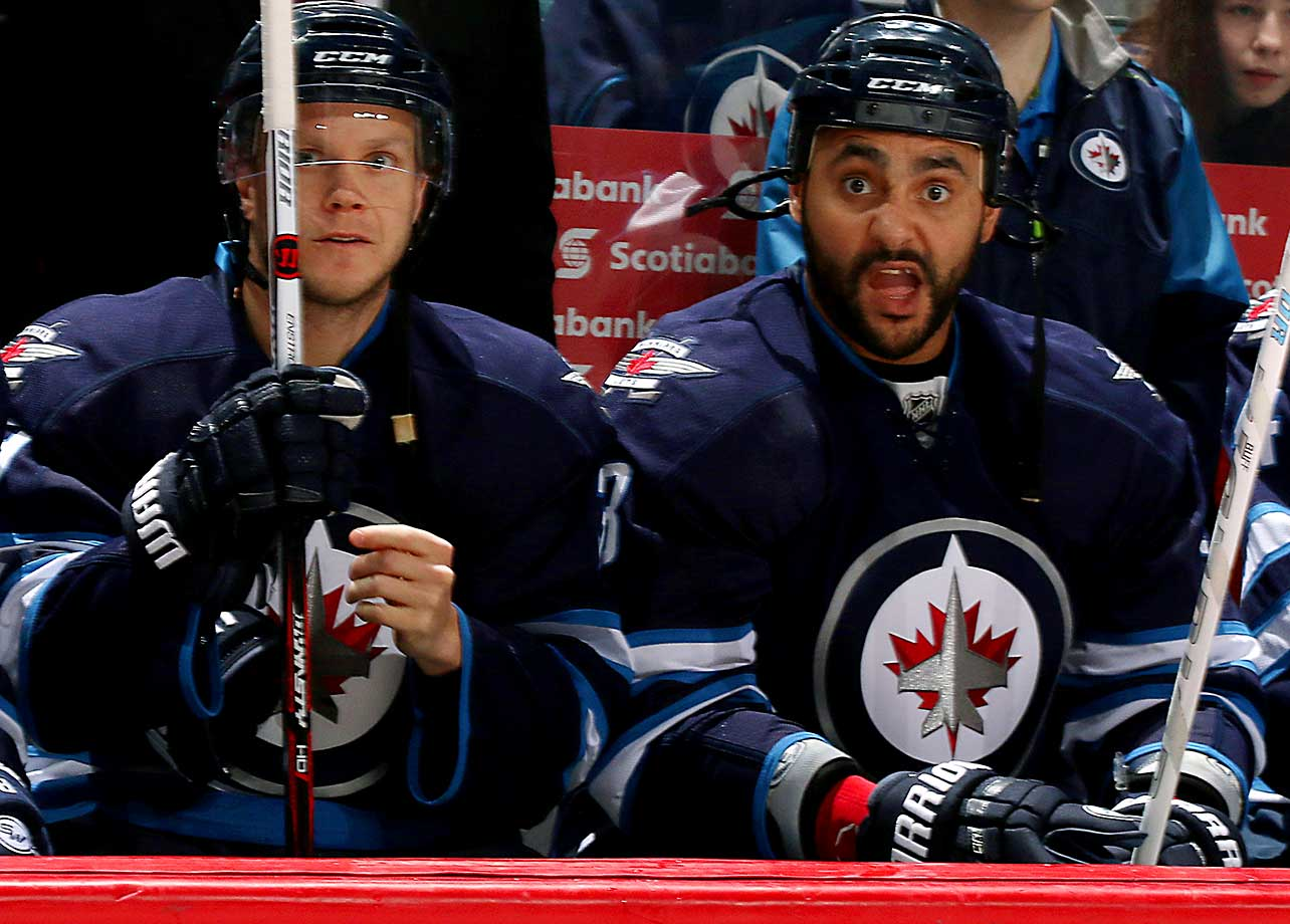 Toby Enstrom, left, and Dustin Byfuglien of the Winnipeg Jets look on from the bench prior to puck drop against the Carolina Hurricanes at the MTS Centre in Winnipeg, Manitoba, Canada.