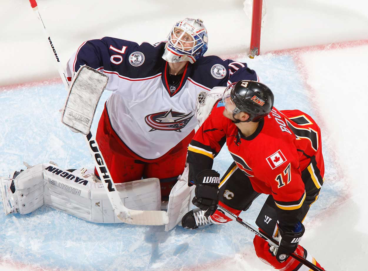 Joonas Korpisalo of the Columbus Blue Jackets keeps his eye on the puck against Lance Bouma of the Calgary Flames.