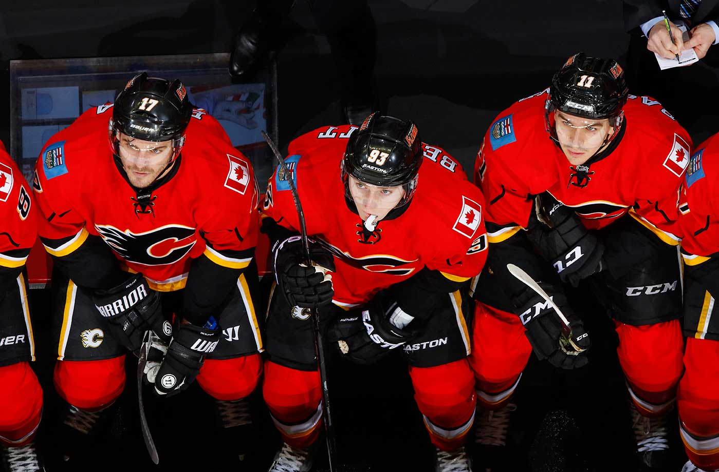 Lance Bouma (17), Sam Bennett (93) and Mikael Backlund (11) of the Calgary Flames look up at the scoreboard during the game against the Columbus Blue Jackets at Scotiabank Saddledome in Calgary.