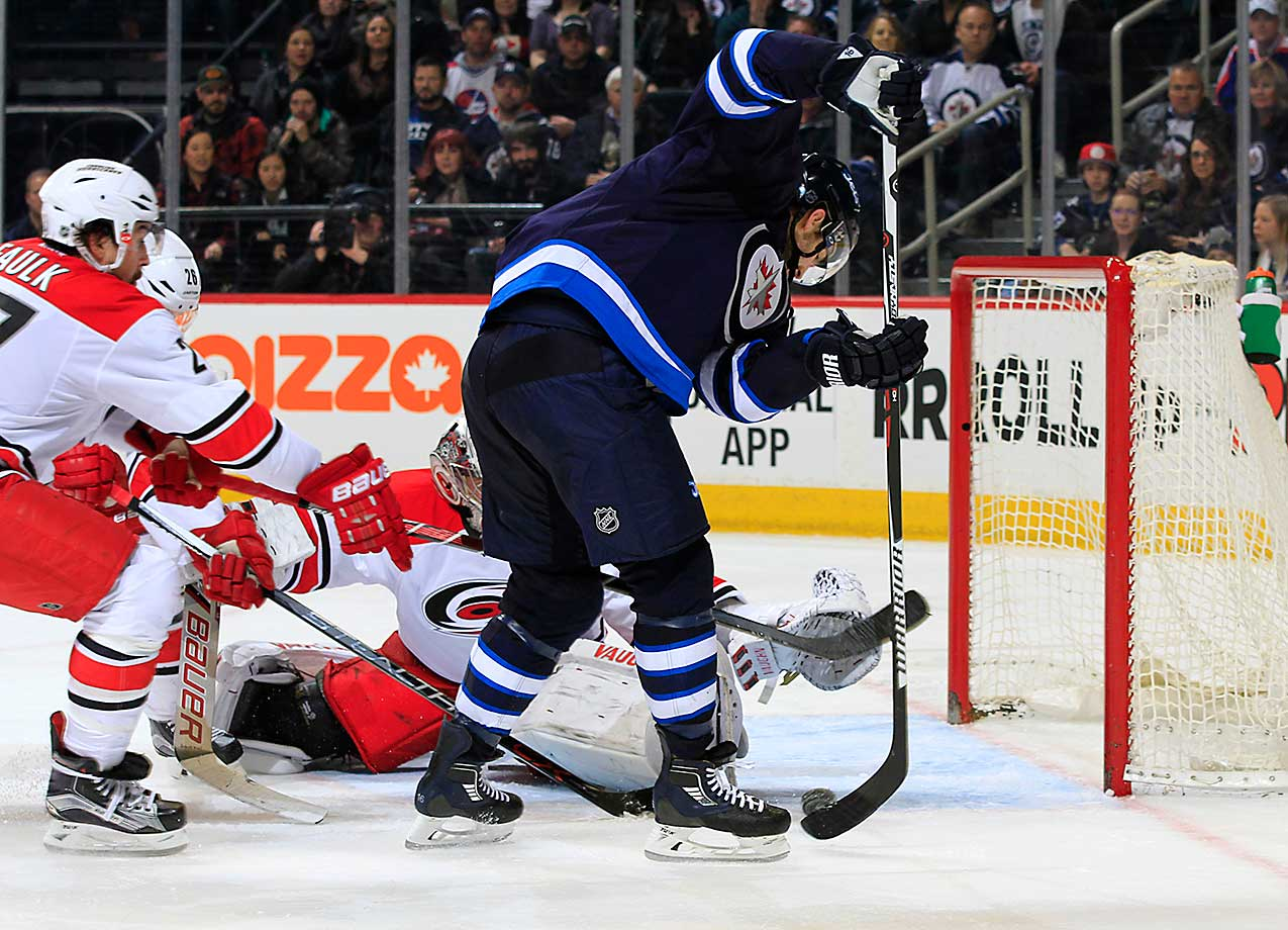 Andrew Ladd of the Winnipeg Jets chips the puck towards the open net past the outstretched arm of goaltender Cam Ward of the Carolina Hurricanes for a third-period goal at the MTS Centre in Winnipeg, Manitoba, Canada.