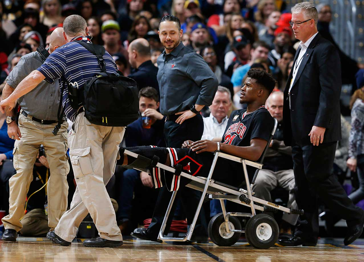 Chicago Bulls guard Jimmy Butler is wheeled off the court after an injury late in the first half of the team's game against the Nuggets in Denver.
