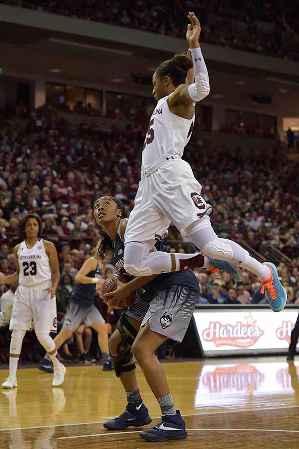 Tiffany Mitchell of South Carolina jumps while defending Morgan Tuck of the Connecticut Huskies. UConn won 66-54.
