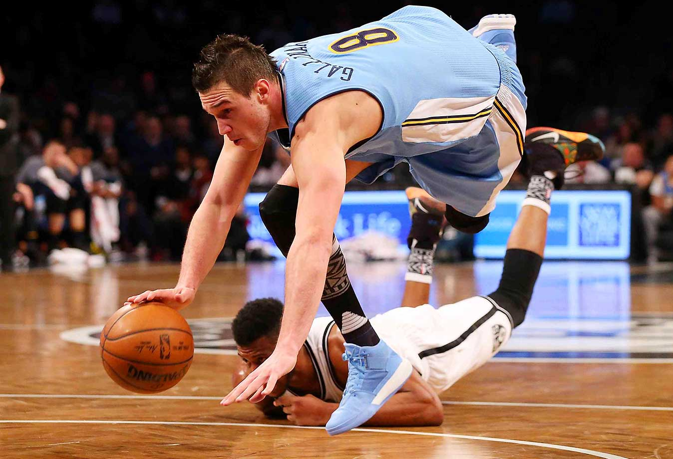 Danilo Gallinari of the Denver Nuggets is tripped up by Thaddeus Young of the Brooklyn Nets.