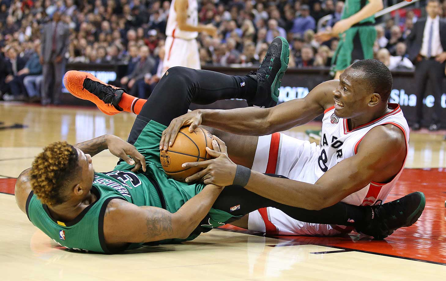 Marcus Smart of the Boston Celtics battles for a ball against Bismack Biyombo of the Toronto Raptors.