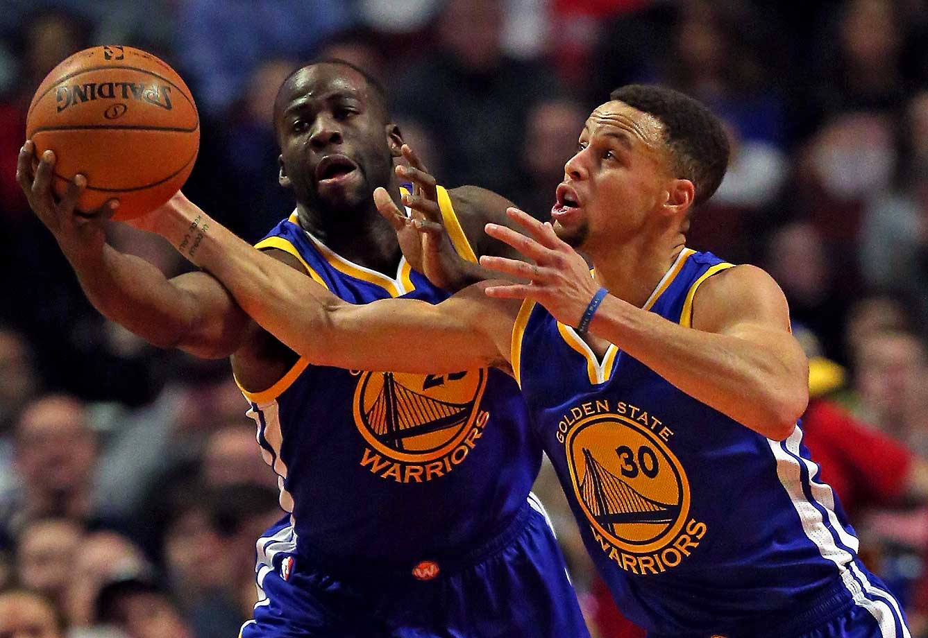 Draymond Green and Stephen Curry of the Golden State Warriors go for a rebound against the Chicago Bulls at the United Center in Chicago.