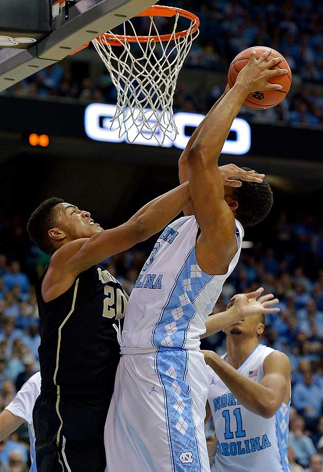 John Collins of the Wake Forest Demon Deacons defends a shot by Kennedy Meeks of the North Carolina Tar Heels at the Dean Smith Center in Chapel Hill.