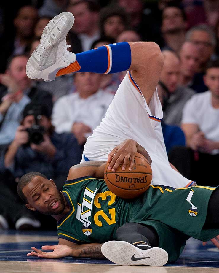 Utah Jazz forward Chris Johnson hangs onto the ball as New York Knicks center Robin Lopez trips over him. The Knicks won 118-111.