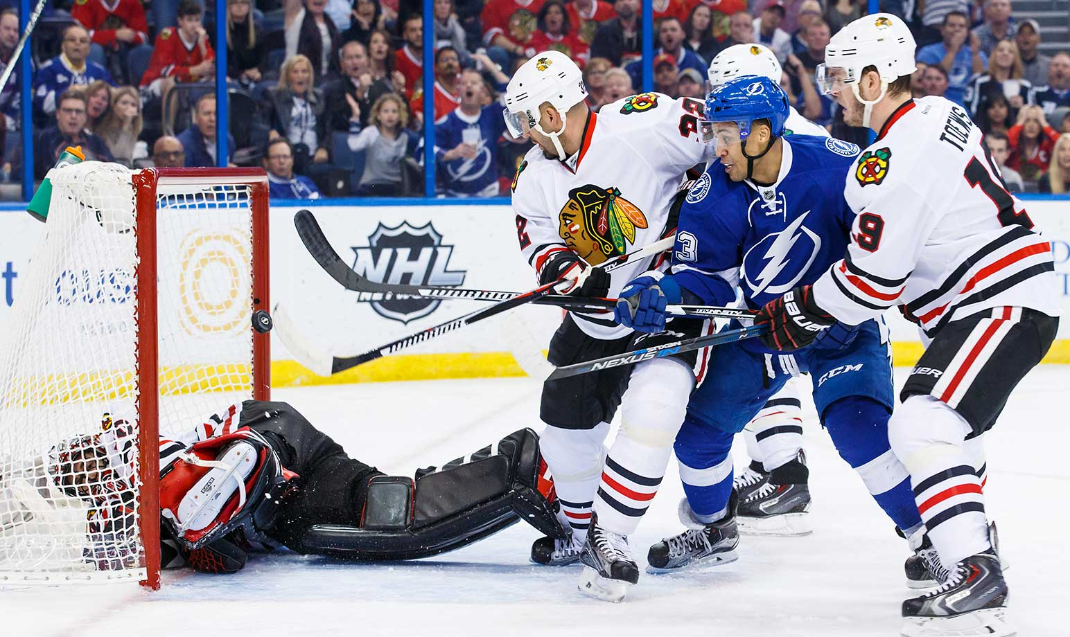 J.T. Brown of the Tampa Bay Lightning shoots the puck while goalie Corey Crawford of the Chicago Blackhawks makes a save and Michal Rozsival (32) and Jonathan Toews (19) look for a rebound at the Amalie Arena in Tampa.