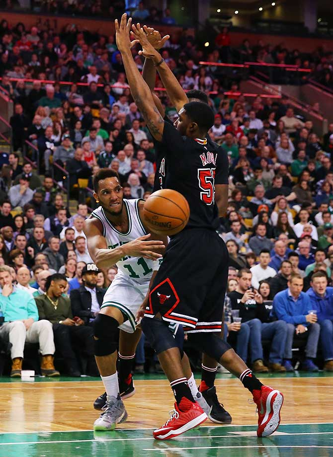 Evan Turner of the Boston Celtics makes a pass around E'Twaun Moore of the Chicago Bulls at TD Garden in Boston.