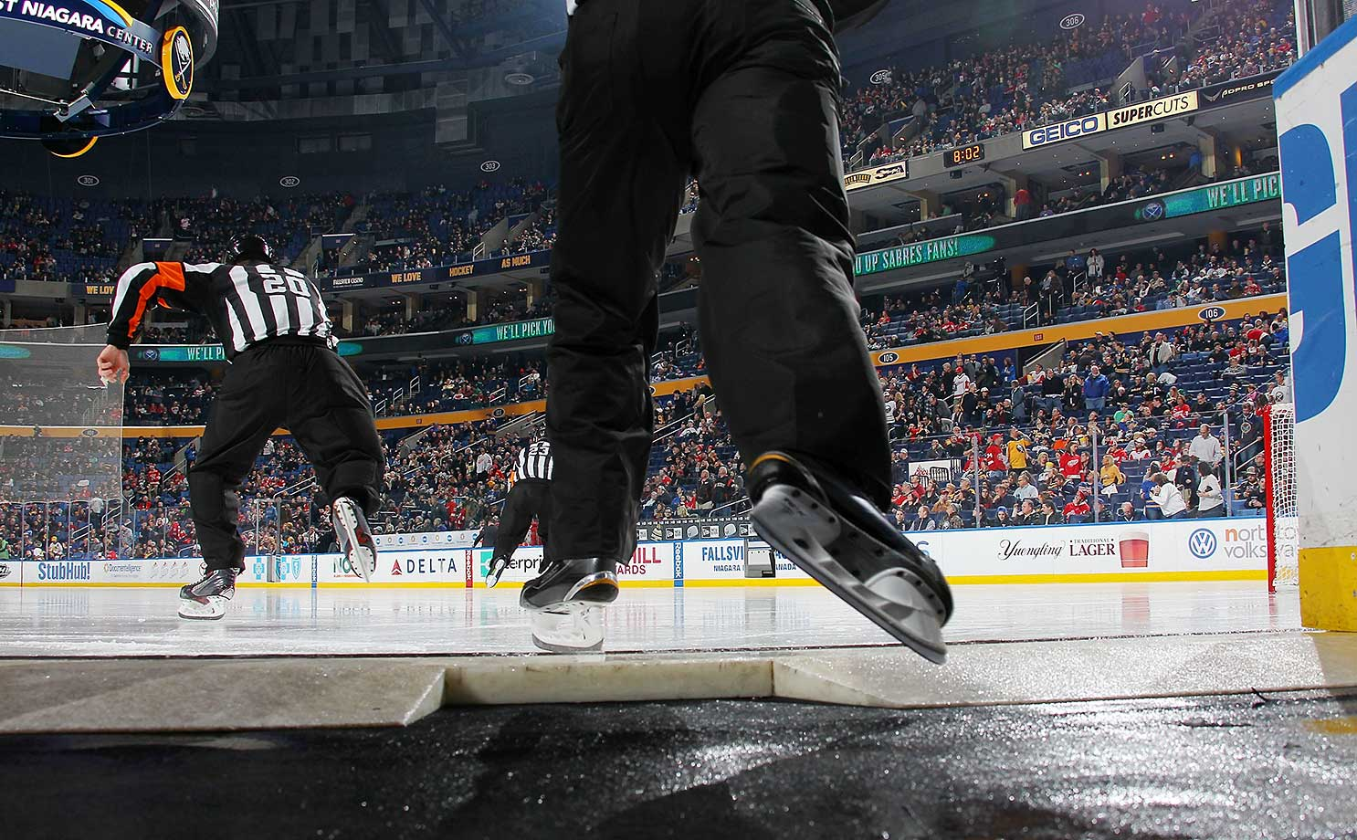 Referee Tim Peel and linesman Greg Devorski skate onto the ice to officiate the NHL game between the Buffalo Sabres and the Detroit Red Wings at the First Niagara Center in New York.