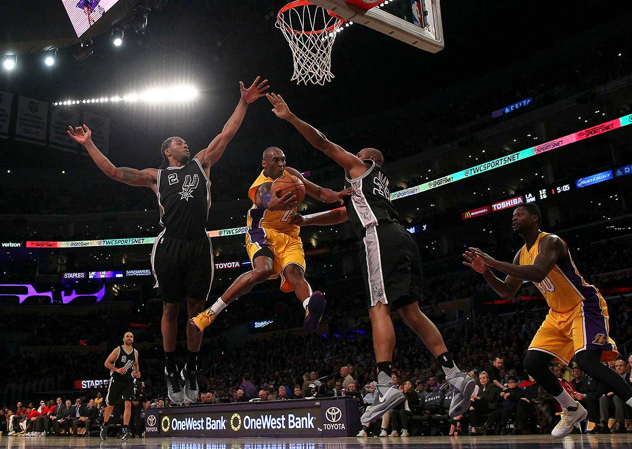 Kobe Bryant of the Los Angeles Lakers looks to make a pass between Kawhi Leonard and Boris Diaw of the San Antonio Spurs in Los Angeles.