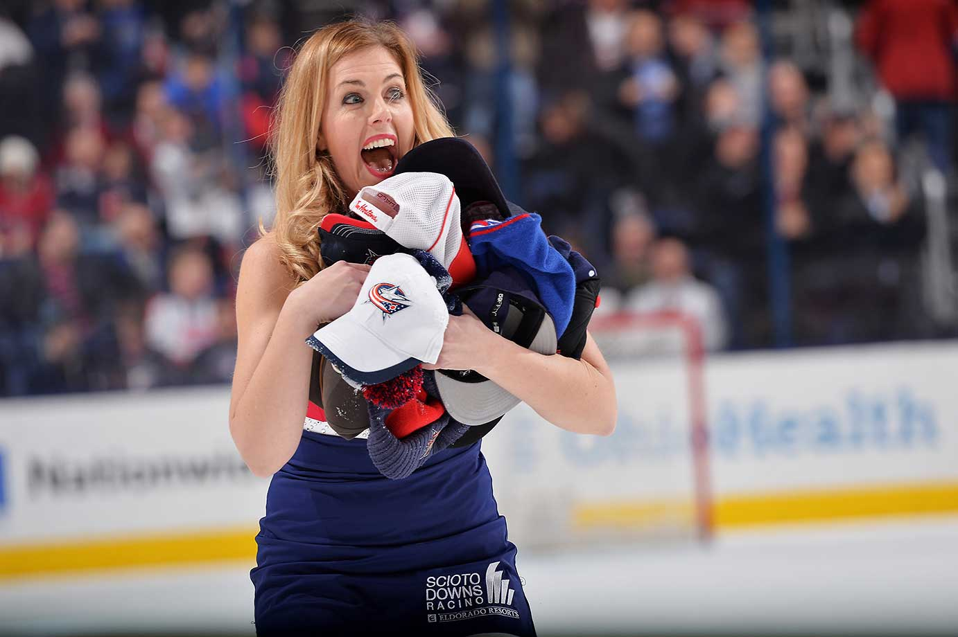 A Columbus Blue Jackets ice girl reacts while picking up hats during the third period of a game against the Montreal Canadiens.