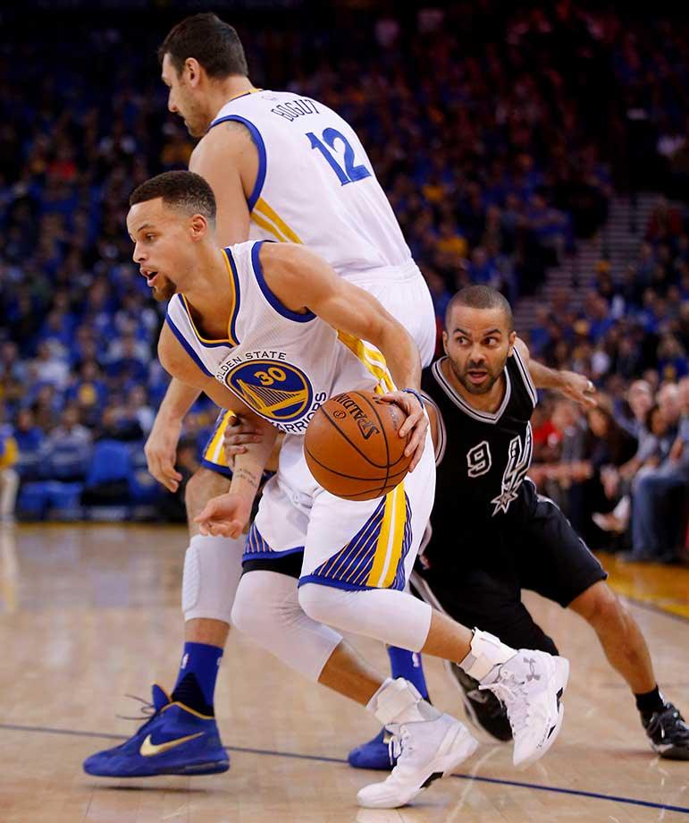 Steph Curry goes around a pick set by Andrew Bogut while he is covered by Tony Parker of the San Antonio Spurs.