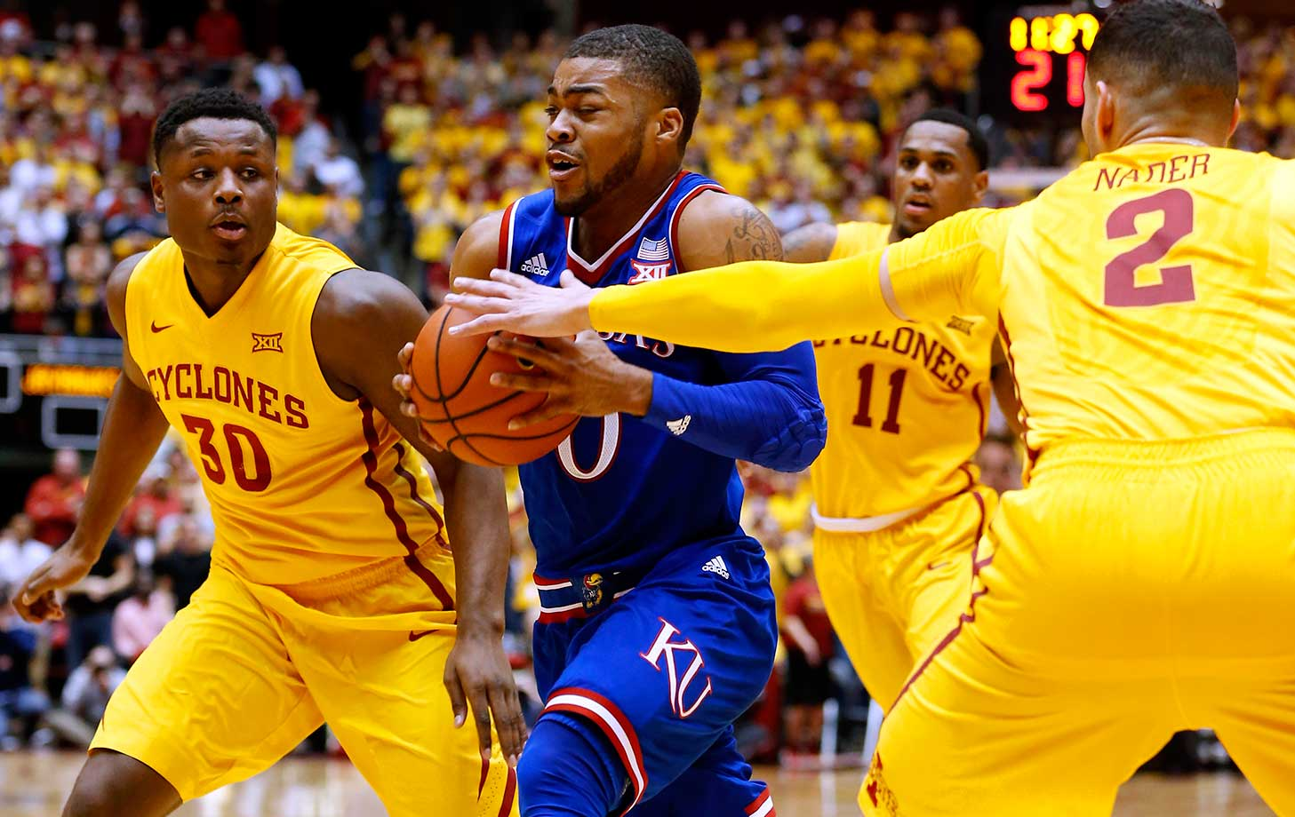 Frank Mason III of the Kansas Jayhawks drives then ball as Deonte Burton (left), Monte Morris (11) and Abdel Nader (2( of the Iowa State Cyclones put pressure on in Ames, Iowa. The Cyclones won 85-72.