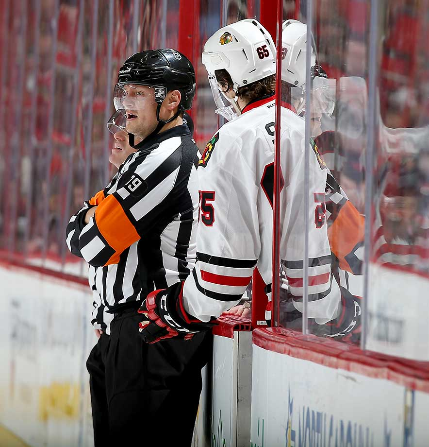 Andrew Shaw of the Chicago Blackhawks has a discussion with referee Evgeny Romasko after being called for interference during a game against the Carolina Hurricanes at PNC Arena in Raleigh, N.C.