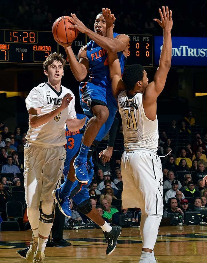 KeVaughn Allen of the Florida Gators takes a shot between Luke Kornet and Jeff Roberson of the Vanderbilt Commodores at Memorial Gym in Nashville.