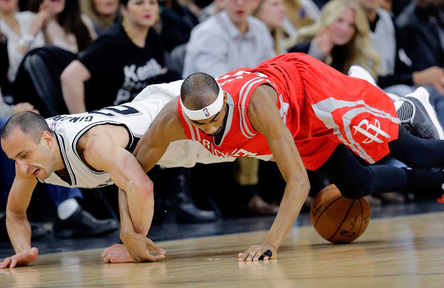 Houston Rockets guard Corey Brewer and San Antonio Spurs guard Manu Ginobili chase a loose ball  in San Antonio.