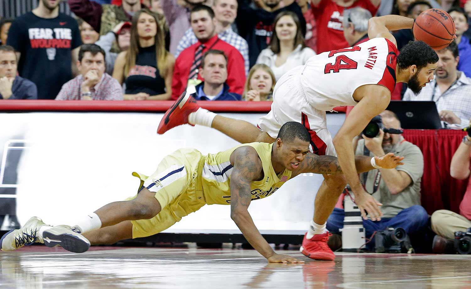 Georgia Tech's Marcus Georges-Hunt chases the ball as  North Carolina State's Caleb Martin dribbles during a game in Raleigh, N.C. Georgia Tech won 90-83.