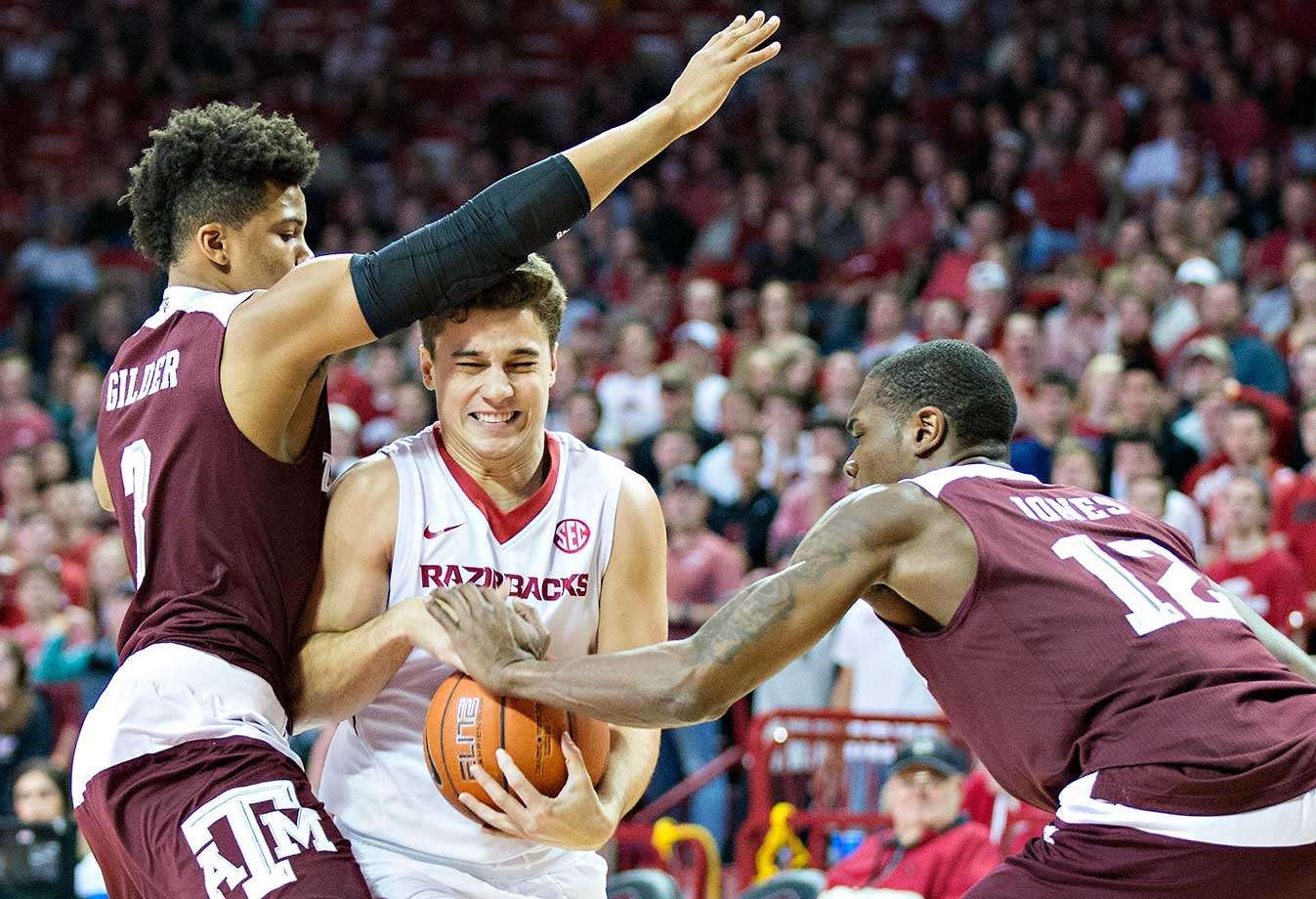 Dusty Hannahs of the Arkansas Razorbacks drives to the basket and is fouled by Jalen Jones of the Texas A&M Aggies at Bud Walton Arena in Fayetteville.  The Razorbacks won 74-71.