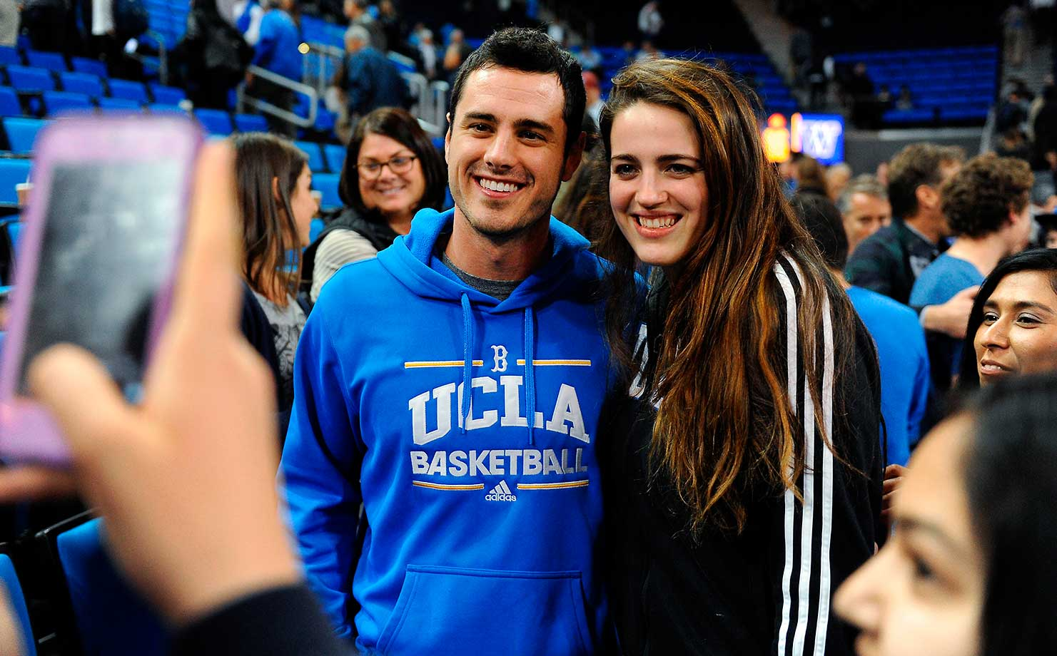 "Ben Higgins from the television show ""The Bachelor"" poses with UCLA student and women's volleyball player Alexa Dreyer after a college basketball game between UCLA and Washington in Los Angeles."