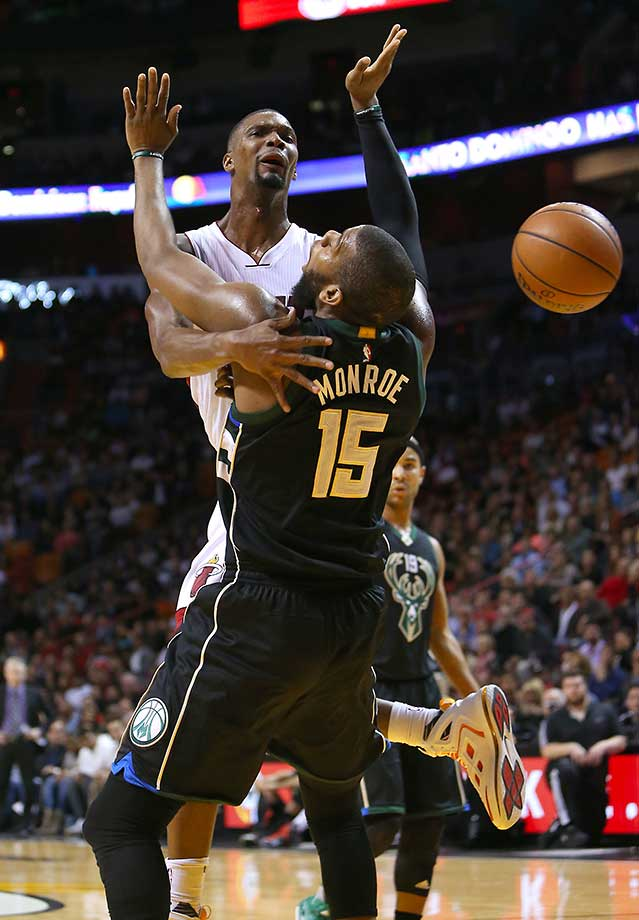 Chris Bosh passes the ball against the Milwaukee Bucks' Greg Monroe at the AmericanAirlines Arena in Miami.