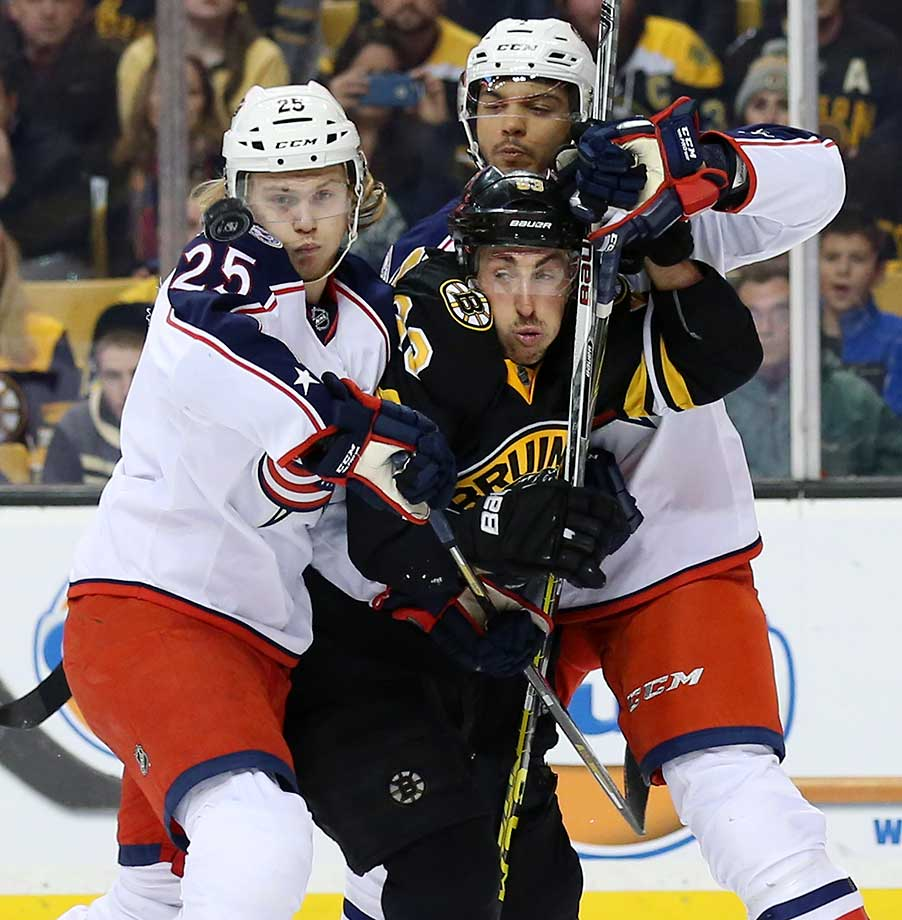The puck comes off the shoulder of Columbus Blue Jackets center William Karlsson (25) as he and defenseman Seth Jones sandwich Boston Bruins left wing Brad Marchand.
