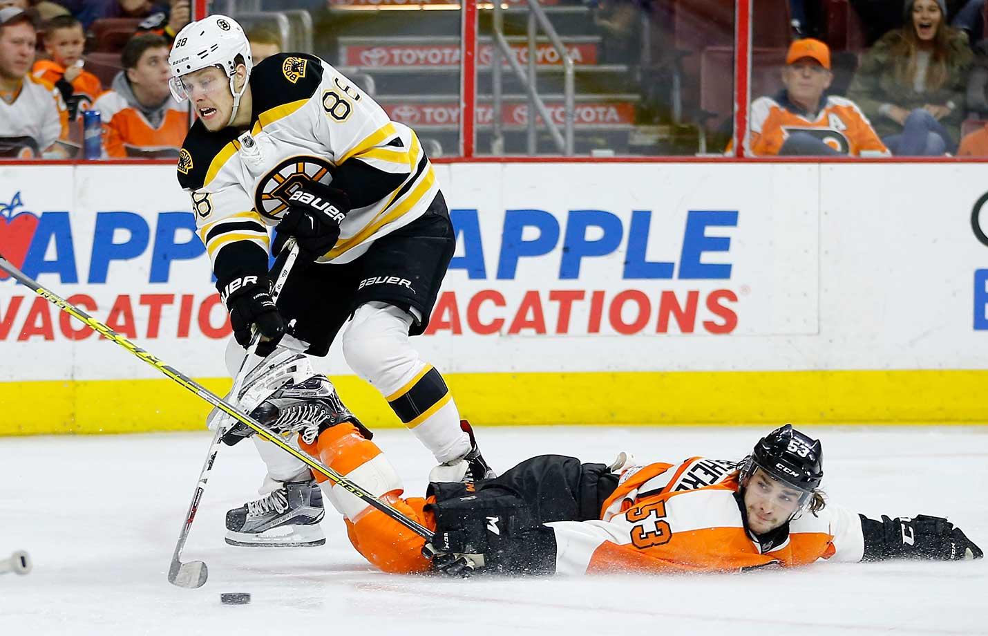 Philadelphia Flyers' Shayne Gostisbehere tries to block a shot by Boston Bruins' David Pastrnak in Philadelphia. Boston won 3-2.