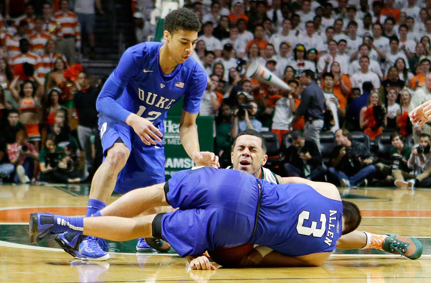 Miami guard Angel Rodriguez grimaces as Duke guard Grayson Allen lands on Rodriguez' arm as they battle for a lose ball in Coral Gables, Fla. Miami won 80-69.