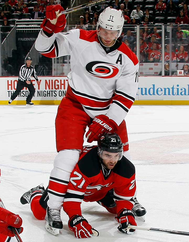 Jordan Staal (11) of the Carolina Hurricanes checks Kyle Palmieri of the New Jersey Devils.
