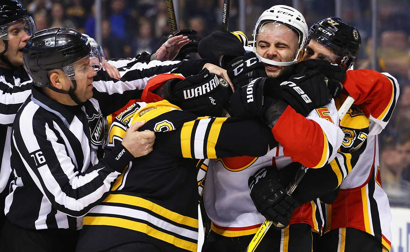 Brad Marchand (63) of Boston and Mark Giordano of Calgary fight at TD Garden in Boston.