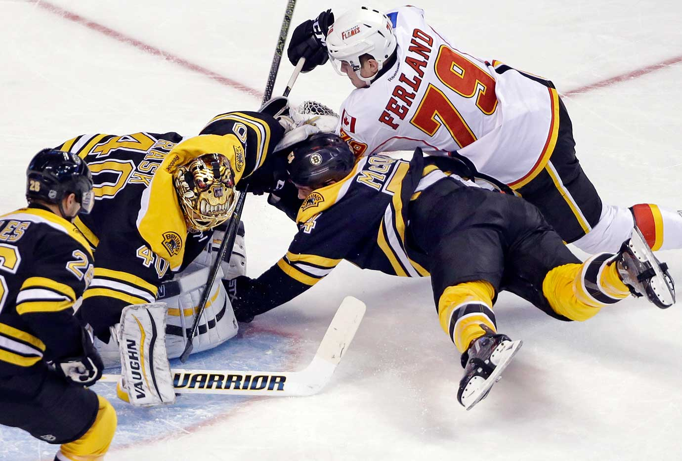 Boston Bruins defenseman Adam McQuaid dives for the puck to prevent Calgary's Micheal Ferland from scoring.