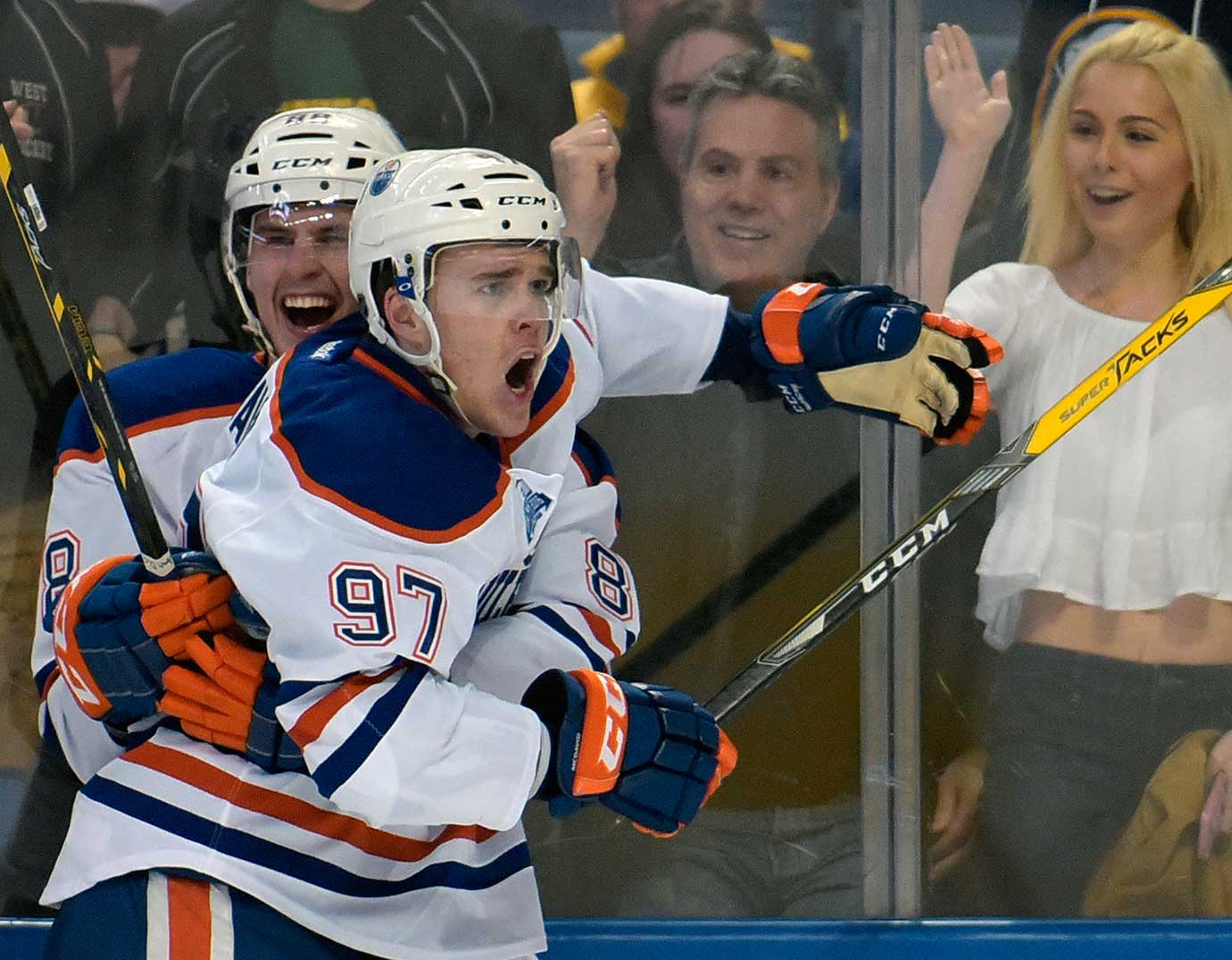 Brandon Davidson, left, celebrates with Connor McDavid after the latter scored in OT to give Edmonton a 2-1 win at Buffalo.