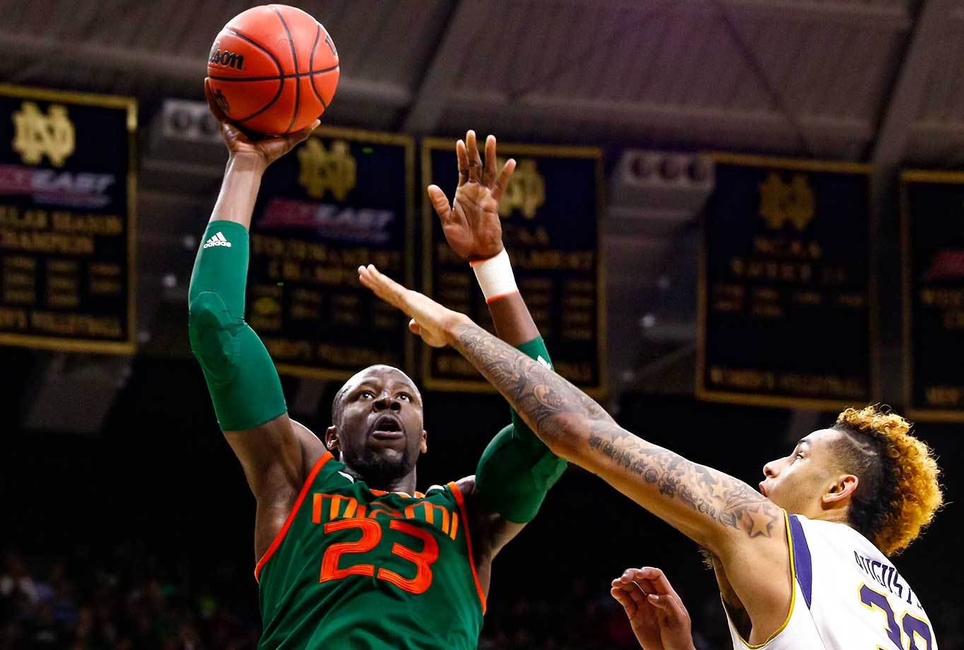 Tonye Jekiri of the Miami Hurricanes shoots against Zach Auguste of the Notre Dame Fighting Irish.