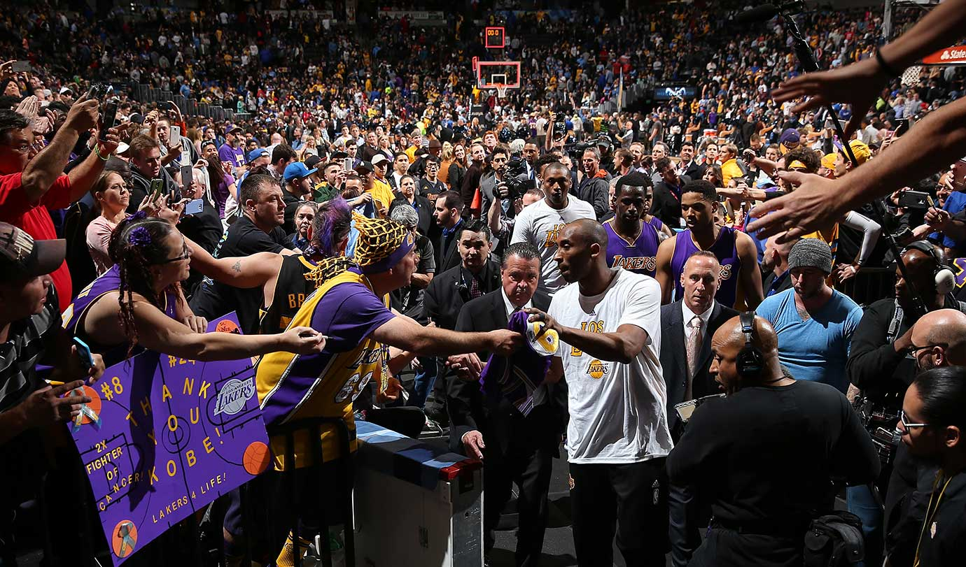 Kobe Bryant passes through a sea of fans as he leaves the court after playing his last game in Denver.
